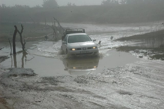 Vehículo atravesando el vado inundado por lluvias del pantano de Los Palacios