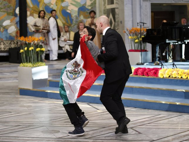 Un joven irrumpe con la bandera de México
