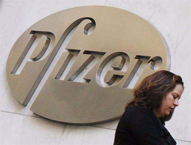 Una mujer camina frente a la sede de la farmacéutica Pfizer en Nueva York