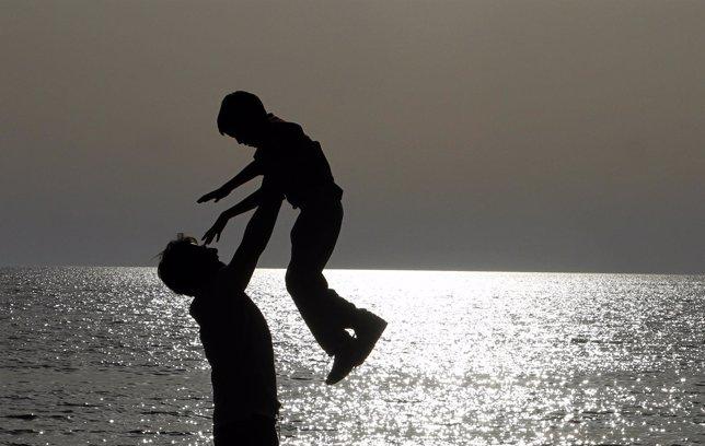 Un hombre juega con su hijo en el mar