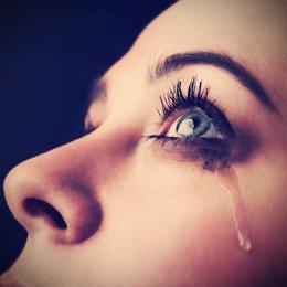 Mujer llorando y una lágrima