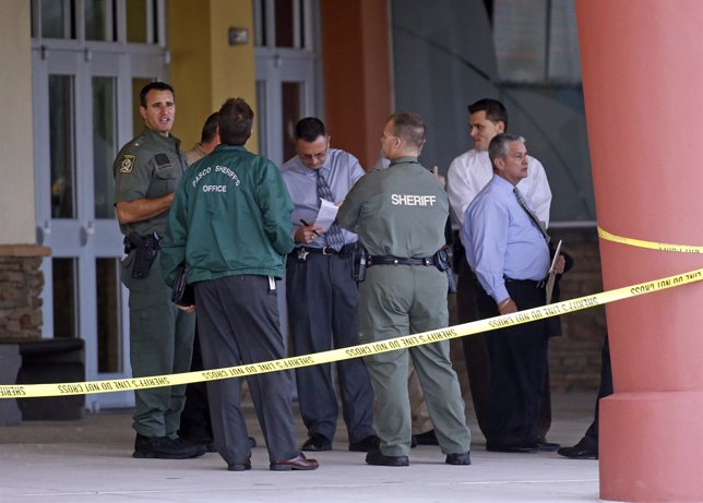 Pasco County Sheriff Chris Nocco speaks with investigators as police tape surrou