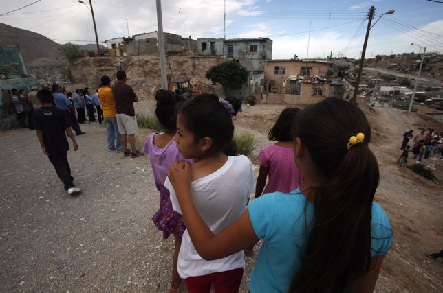 Residents stand near the site of a landslide in an impoverished neighbourhood in