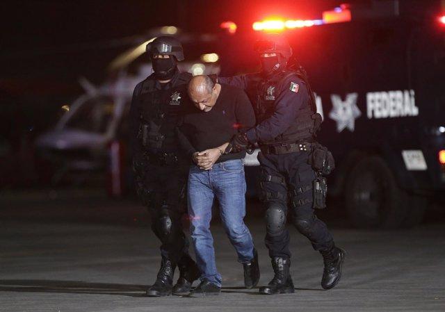 "Servando ""La Tuta"" Gomez is being escorted by police officers during a media con"