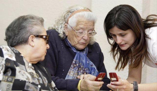 Dos mujeres mayores aprenden a usar el móvil