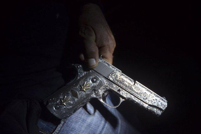 Un ex miembro del cártel de drogas, convertido en vigilante, muestra su arma