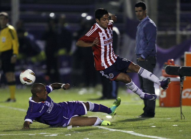 Pintos of Defensor Sporting competes for ball with Nava of Chivas during their C