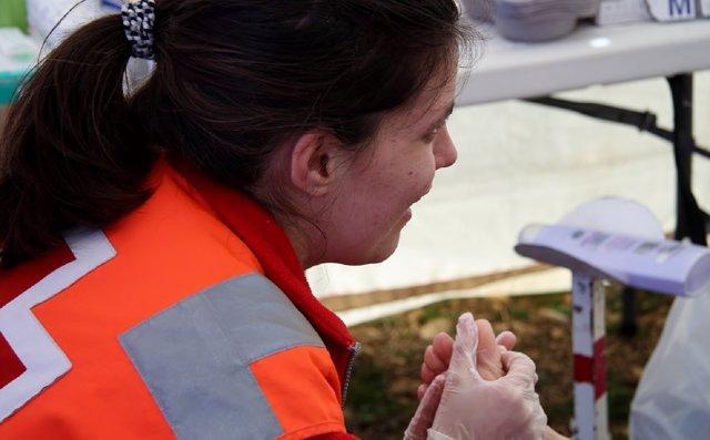 Delegada de Cruz Roja atendiendo a un peregrino