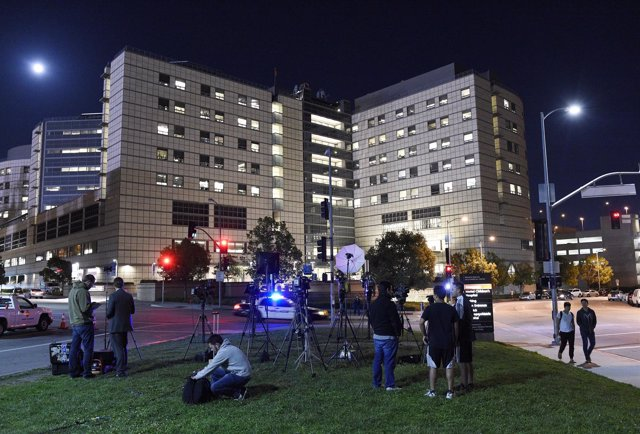 Members of the media wait outside The Ronald Reagan UCLA Medical Center, where a