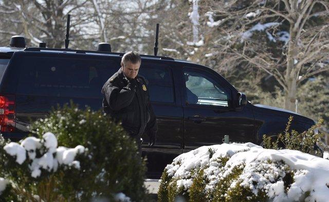 A Secret Service officer radios as a motorcade vehicle prepares to take U.S. Pre