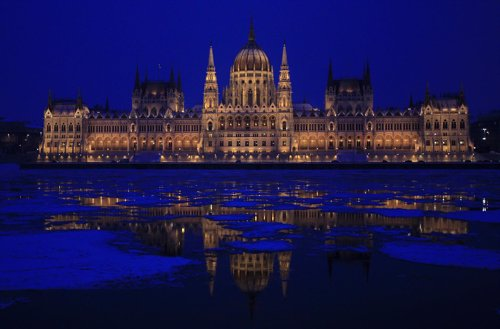 The Hungarian Parliament building is reflected on the icy Danube river in Budape