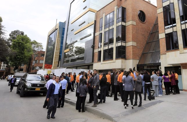 A group of people stand outside their building office after a tremor in Bogota