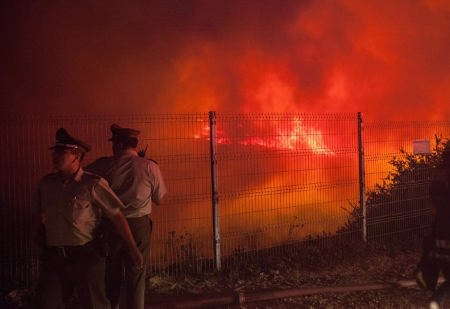 Police officers standby while a forest fire burns the hills of Valparaiso city
