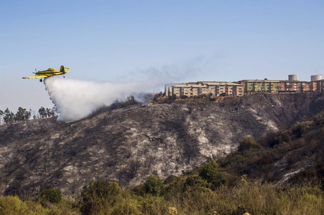 Plane assists in putting out a forest fire at the hills in Valparaiso city