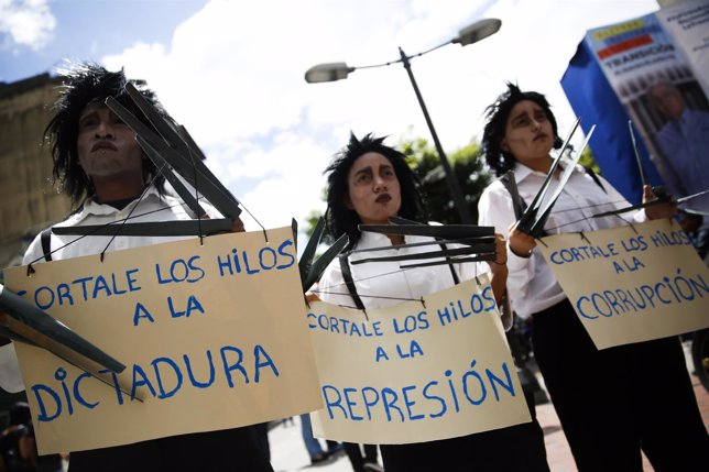 Opposition supporters hold placards during a gathering to protest against Venezu