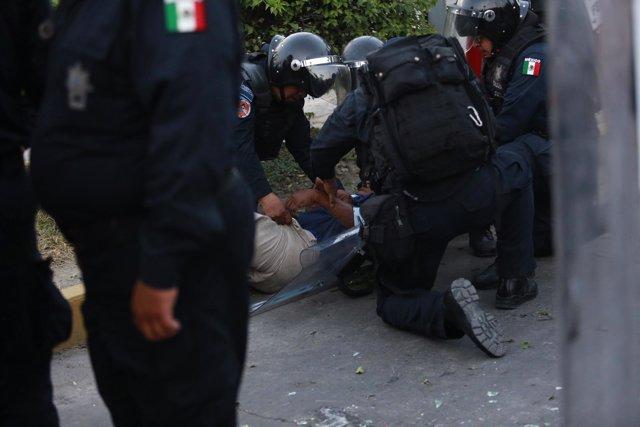 Policias federales deteniendo a un normalista.