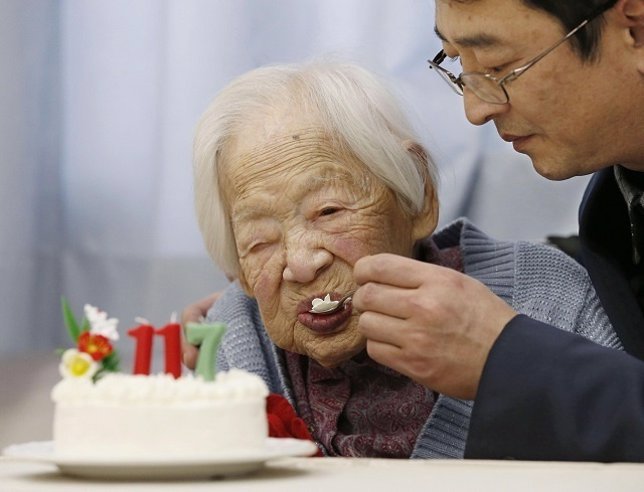 Japanese Okawa, the world's oldest living person, is helped to eat her birthday