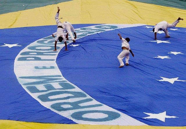 Niños haciendo Capoeira encima de una bandera gigante de Brasil.