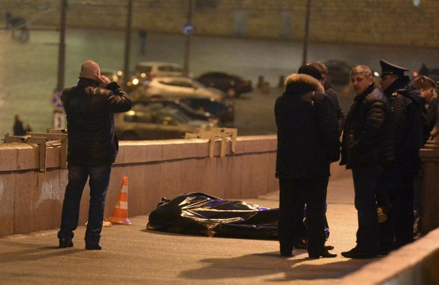 Investigators gather near the covered body of Boris Nemtsov in central Moscow