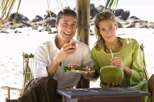 Padre con hija adolescente rubia y muy guapa comen fruta en la plya
