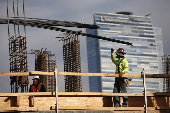 Men work on a construction site for a luxury apartment complex in downtown Los A