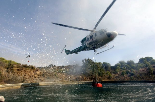 Helicóptero en proceso de repostaje de agua contra incendios