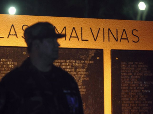 A veteran of Falklands War stands in front of memorial wall, which shows names o