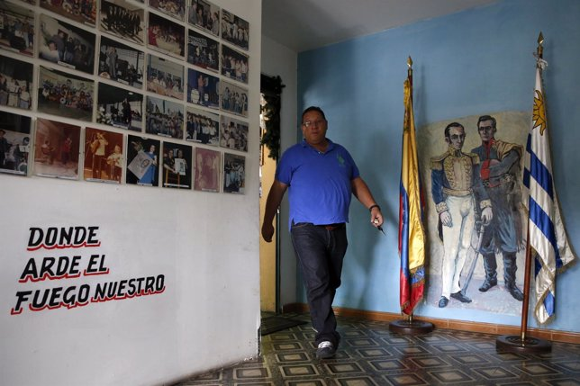 A man walks past a mural depicting Latin American political and military leader