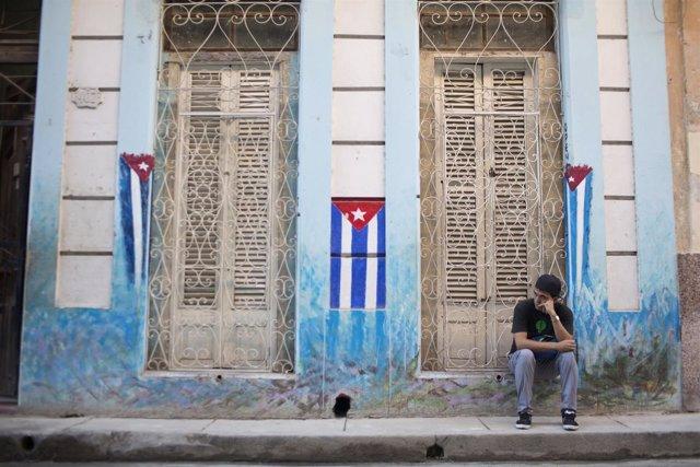 Un hombre sentado en una acera de La Habana, Cuba, con las banderas nacionales.