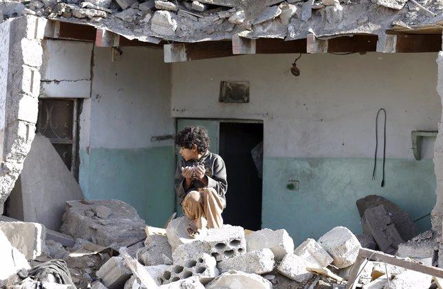 Un niño sobre un montón de escombros en Saná