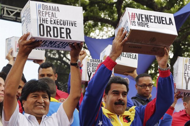 Venezuela's President Maduro and his Bolivian counterpart Morales carry boxes co
