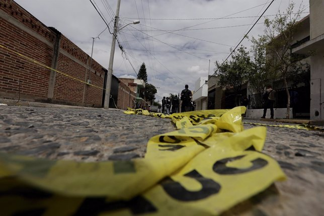 Yellow police tape lies on the road as federal agents work at a crime scene in t