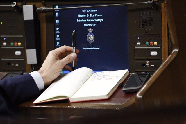 Pedro Sánchez con un libro en su escaño en el Congreso