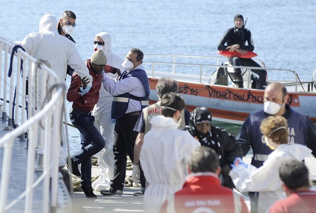 Migrants are helped as they disembark from a Coast Guard boat in the Sicilian ha