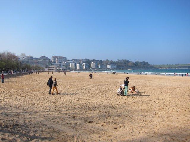 Gente pasenado por la playa en Santander