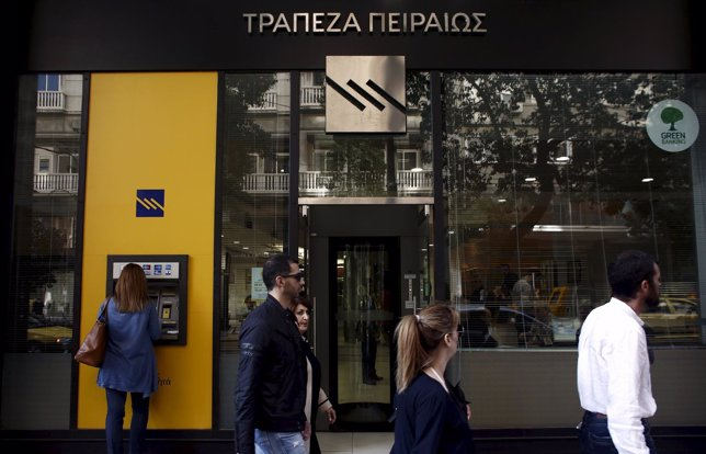 A customer uses an ATM outside a branch of Piraeus Bank in Athens