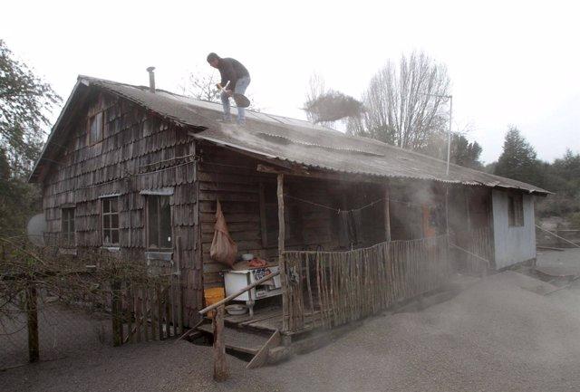 Un hombre retira la ceniza del volcán Calbuco del tejado de su casa.