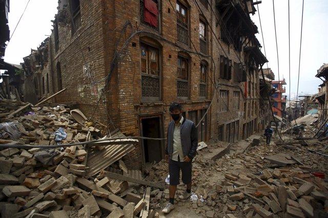 Un hombre delante de casas derruidas por terremoto en Nepal