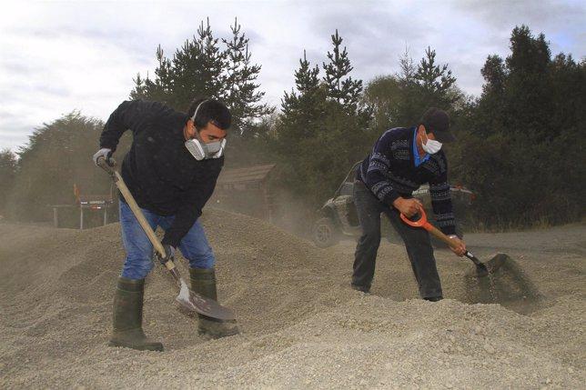 Men shovel ash from Calbuco volcano off a road in Ensenada
