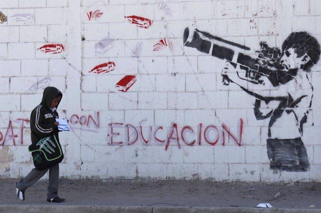 Un niño camina por Ciudad Juárez, México, delante de mural con un niño armado