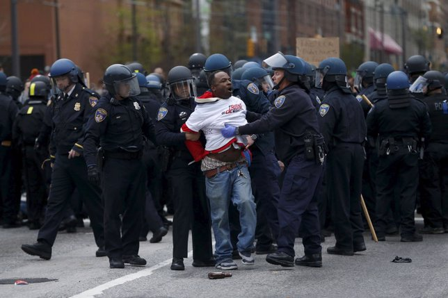 Police detain a protester at a rally to protest the death of Freddie Gray who di