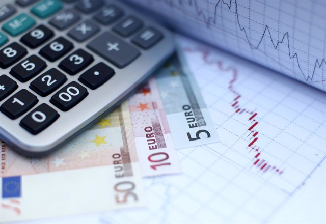 Euro banknotes coins and a calculator are placed on a currency graph and ticker