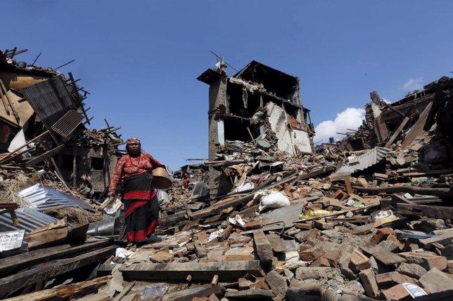 Una mujer sobre los escombros en Nepal tras el terremoto