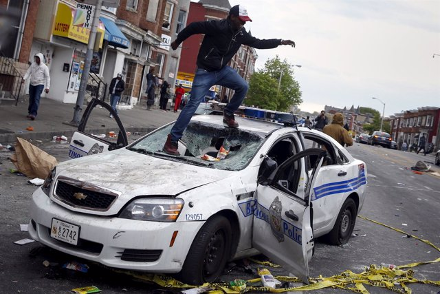 Demonstrators jump on a damaged Baltimore police department vehicle during clash