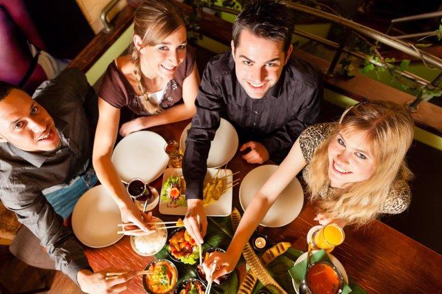 Jóvenes comensales compartiendo mesa en Tailandia