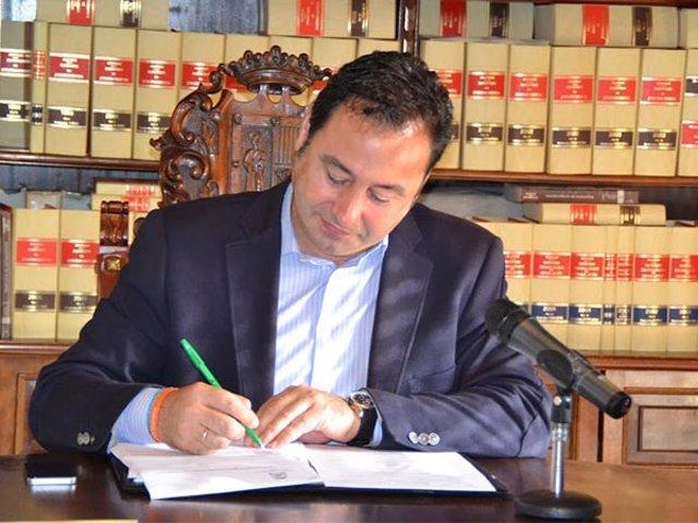 El alcalde firma el convenio.
