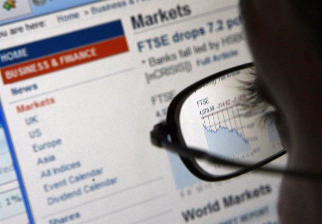 Un hombre observa una pantalla con información financiera