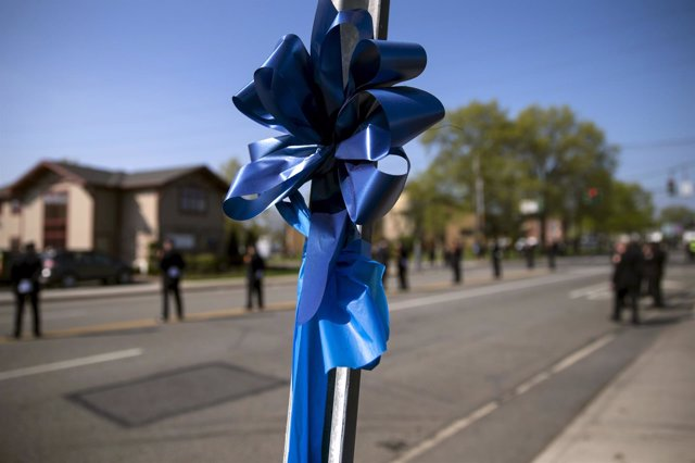 Blue ribbon is seen tied to a sign post outside the funeral service for slain Ne