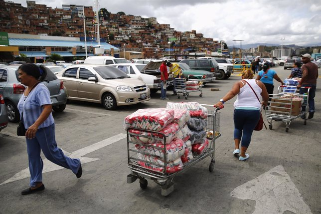 A woman pulls a cart with bags of rice outside Makro supermarket in Caracas