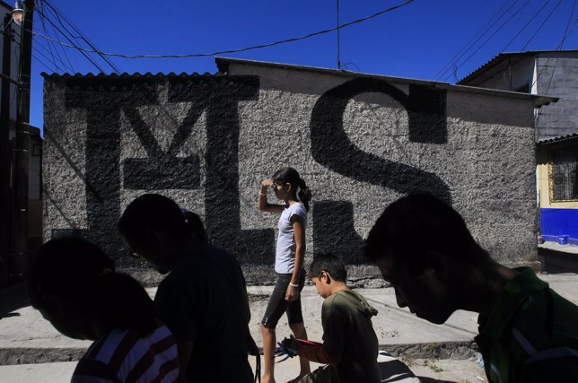 Residents walk past graffiti on the walls of a building showing the letters